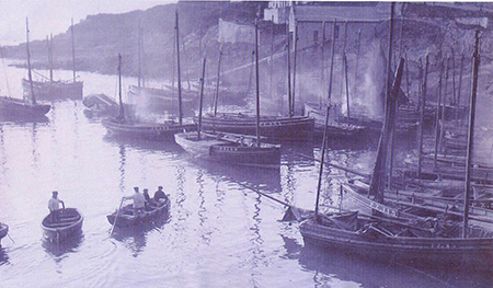 An early photograph of The Lifeboat House c1900 with sailing ships in the foreground.