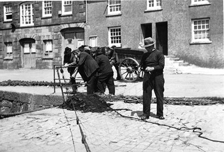 Edward James Williams mending nets in front of Old Customs House