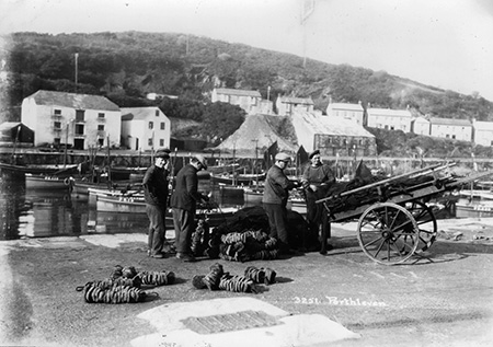 Fishermen mending their nets. The China Clay Store can be seen in the background.