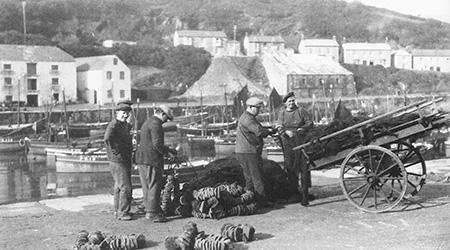Porthleven fishermen mending their nets. Again the Ice House can be seen in the background.